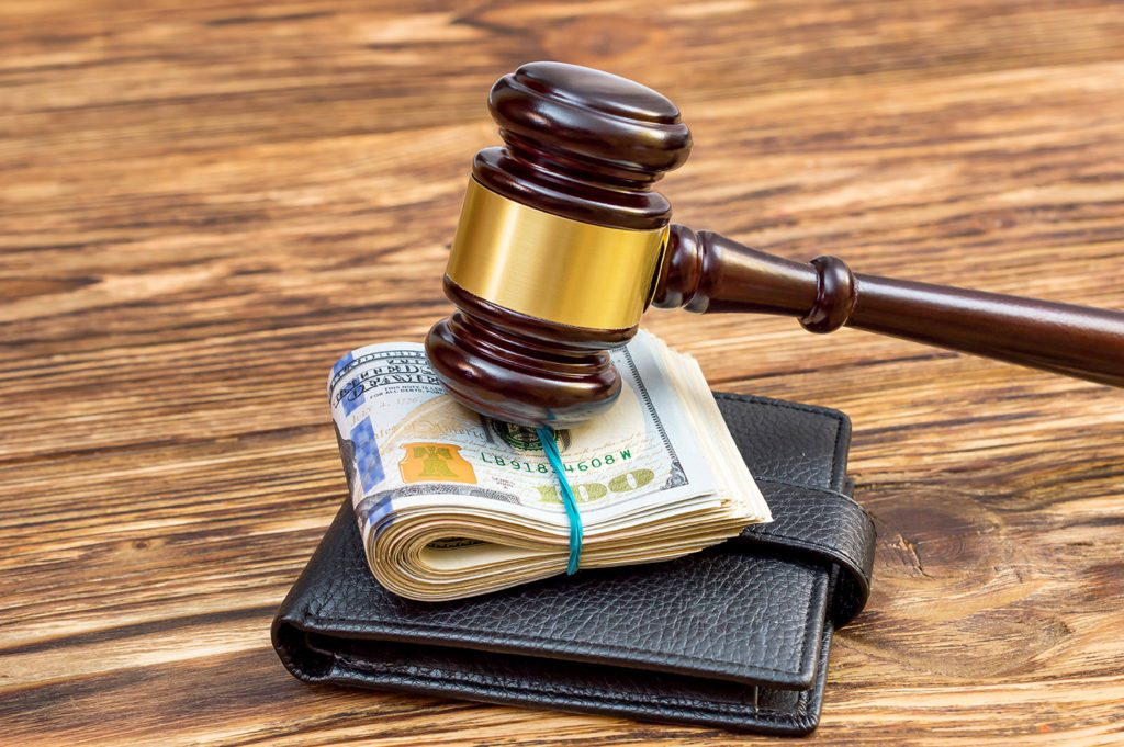 Gavel on a wallet, representing person with wage garnishment needing a bankruptcy lawyer.