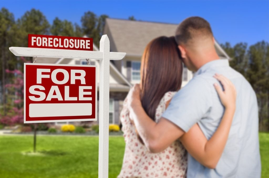 Couple looking at their foreclosed home