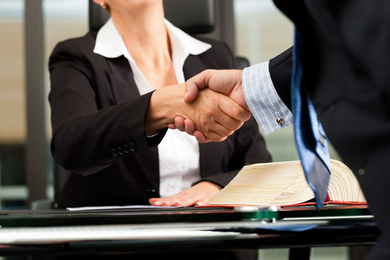 Lawyer shaking hands with her client