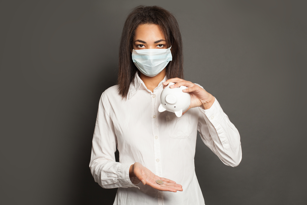 Woman wearing medical mask holding piggy bank upside down