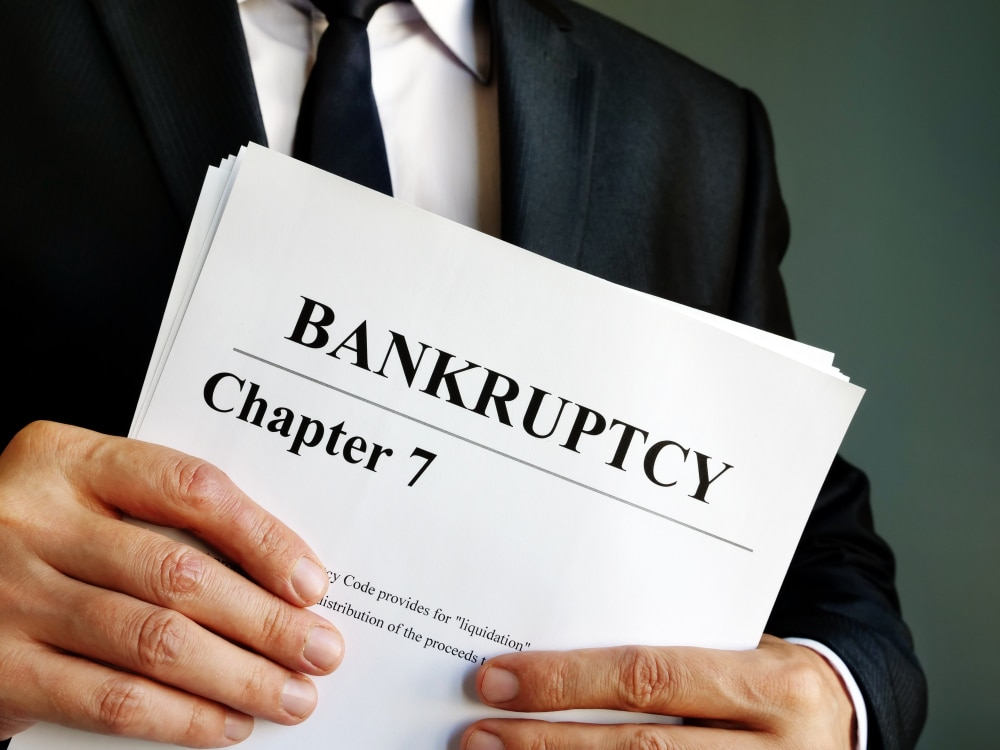 Well-dressed man holding papers that say Bankruptcy Chapter 7